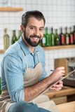 Idérik ung man som ler, medan skriva en meny för ett kafé Arkivfoto