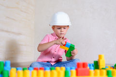 Idérik ung pojke som spelar med byggnadskvarter Royaltyfri Bild