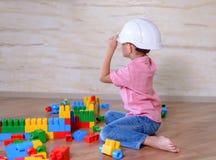 Idérik ung pojke som spelar med byggnadskvarter Arkivfoto