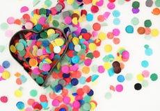 Idérik vinterbakgrund med den hjärta formade bakningformen som fylls med färgrika papperskonfettier arkivfoto