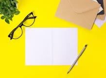 Idérik workspace med kuvert på gul bakgrund royaltyfria foton