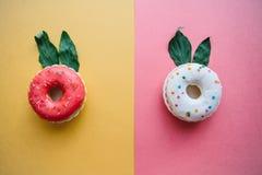 Idérika donuts med öron av sidor som är liknande till en kanin på blommabakgrunder i en minsta stil Royaltyfri Bild
