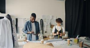 Idérika sömmerskor som planlägger kläder genom att använda minnestavlan och mått-bandet i studio arkivfilmer
