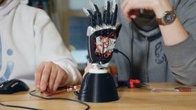 Idérika teknikerer på modernt startar upp kontoret att arbeta med den innovativa bioniska robotic armen Dockakamerarörelse arkivfilmer