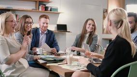 Idérikt affärslag på tabellen i ett modernt startup kontor den kvinnliga högtalaren erbjuder en stor idé, och laget stöttar henne Arkivfoto
