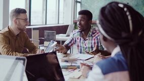 Idérikt affärslagmöte i modernt kontor Grupp för blandat lopp av ungdomarsom diskuterar start-up idéer som skrattar