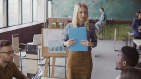 Idérikt affärsmöte av laget för blandat lopp Kvinnalagledare som framlägger till den nya idén för grupp människor på det moderna  lager videofilmer