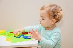 Idérikt barn som hemma gjuter och att spela med plasticine Royaltyfria Bilder