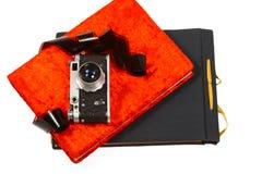 Idérikt begrepp av en tappningkamera och färgrika fotoalbum som isoleras på vitbakgrund Royaltyfria Bilder