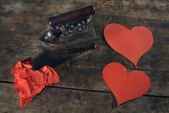 Idérikt förälskelsebegrepp som stryker rynkiga hjärtor på en härlig gammal tabell royaltyfria bilder