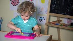 Idérikt flickabarn som drar det magnetiska brädet för nolla som sitter vid tabellen arkivfilmer