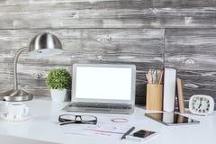 Idérikt kontorsskrivbord med den tomma vita bärbara datorn royaltyfria foton