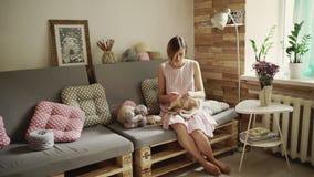 Idérikt kvinnasammanträde på woolen kläder för soffa och för handarbete lager videofilmer