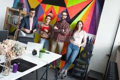 Idérikt lag av fyra kollegor som arbetar i modernt kontor Fotografering för Bildbyråer
