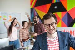 Idérikt lag av fyra kollegor som arbetar i modernt kontor Arkivbild