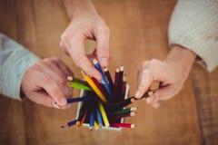 Idérikt lag som väljer olika färgade blyertspennor Fotografering för Bildbyråer