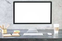 Idérikt skrivbord med den rena vita datorskärmen fotografering för bildbyråer