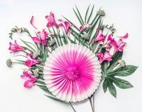 Idérikt tropiskt komponera med exotiska blommor, palmblad och den rosa partipappersfanen på vit bakgrund, bästa sikt blom- round arkivbilder