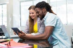 Idérikt ungt affärsfolk som ser den digitala minnestavlan Royaltyfri Fotografi