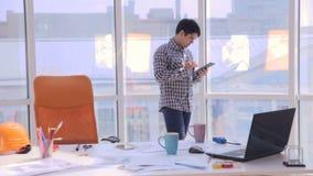 Idérikt ungt yrkesmässigt arbete på det moderna kontoret Gå på arbetsplatsen i tankar stopptid lager videofilmer