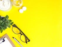 Idérikt workspaceskrivbord på ljus gul bakgrund arkivfoto