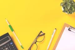 Idérikt workspaceskrivbord på ljus gul bakgrund royaltyfri foto