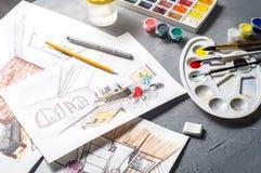 Idérikt yrke: det märkes- skrivbordet för ` s med spritt skissar, målarfärger, borstar, eyeliner, blyertspenna Royaltyfri Foto