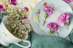 Id?rik sammans?ttning med koppen och blommor arkivbild