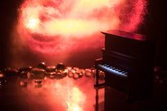 id?rikt begrepp Konstverkgarnering med pianot p? m?rk tonad dimmig bakgrund med ljus arkivbild