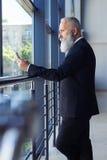 Idade desagradável do senhor de 50-60 que surfam no telefone Imagem de Stock Royalty Free