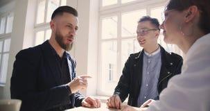Idade diversa feliz fêmea e executivos masculinos que falam entre si formalmente no escritório na moda moderno confortável vídeos de arquivo