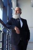 Idade Pokerfaced do homem de 50-60 que olham para fora a janela Fotografia de Stock Royalty Free