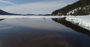 Payette Lake inlet in winter with snow and ice and a few clouds. Idaho mountain lake with trees sticking out of the water with ice stock video footage
