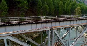 Railroad bridge leading into a forest along a river in Idaho. Idaho river with a train bridges crossing into a forest stock video