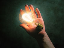 Idea. A glowing bulb in a hand Royalty Free Stock Photos