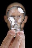 Idea. Man with a lightbulb over his face , representing an idea Royalty Free Stock Photos