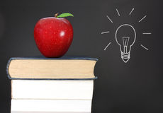 Idea. Apple and books with an idea symbol on a chalkboard in the background Stock Photos