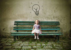 Idea. Little girl sitting on a park bench and having an idea Royalty Free Stock Photo