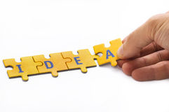 Idea. The word idea built from the puzzle pieces with male hand stock image