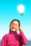 Idea. Bright lamp over happy young girl having an idea Royalty Free Stock Images