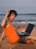 Idea!. Man sitting on the beach with laptop, with one finger up - he had an idea royalty free stock image