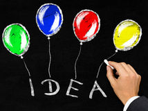 'Idea' with balloons written on blackboard by businessman Royalty Free Stock Image