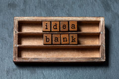 Idea bank concept image. Vintage shelf with blocks text letters, aged wooden box. Gray stone background, macro, soft Stock Images