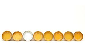 Idea in beer caps decortion. A white cap on golden caps isolation Royalty Free Stock Photo
