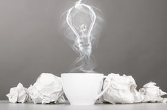 Idea birth. Crumpled wads and bulb silhouette on gray Royalty Free Stock Image