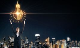 Idea and brainstorm concept. Happy businesswoman with glowing lamp brain on blurry night city background. Idea and brainstorm concept royalty free stock image