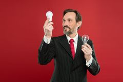 Idea for business. Environment friendly idea. Genius idea. Light up your business. Man bearded businessman formal suit. Hold light bulb on red background stock photography