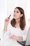 Idea: business woman thinking with pen in hand at Office. Stock Photos