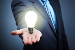 Idea. Businessman with illuminated light bulb balancing on his hand concept for idea, innovation and inspiration