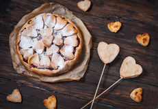 Idea for the celebration of Valentine`s Day: cherry pie with the decor the dough in the shape heart on wooden table.